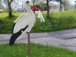 Storch aus Hols mit Baby im Schnabel