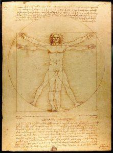Vitruvianischer Mensch, Leonardo Da Vinci. Zeichnug eines nackten Mannes auf verbilbten Papier mit langen Haaren. Die Arme und Beine sind je zweimal gezeichnet. Die beine einmal ausgestreckt, einmal gespreizt. Die arme einmal ausgestreckt, einmal über die Schultern gehoben. Um den Mann sind ein Quadrat und ein Kreis gezeichnet, die sich überschneiden. Die gehobenen Arme und gespreizten Beine liegen am Kreis an. Die gestreckten Arme und Beine berühren das Quadrat. Über und unter dem Mann befindet sich ein Text in Handschrift.