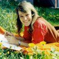 altes Farbfoto von Hannah in der Sonne auf einer Blumenwiese liegend