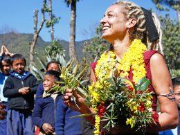 Stella Deetjen mit Blumenkette umgeben von nepalesischen Kindern