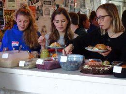 feministisches Frühstück, Drei frauen nehmen sich Speisen bei einem Frühstücksbuffet. Im Hintergrund sind weitere Frauen, die sich Unterhalten. Eine Wand im Hintergrund ist mit Plakaten behangen.