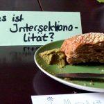 """Ein bestrichenes Brötchen mit Brotaufstrich und einem Buttermesser auf einem Grünen Teller. Davor liegen Flyer von den Frauenseiten. Dahinter steht ein Schildchen mit der Aufschrift """"Was ist Intersektionalität?"""""""