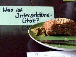 """feministisches Frühstück, Ein bestrichenes Brötchen mit Brotaufstrich und einem Buttermesser auf einem Grünen Teller. Davor liegen Flyer von den Frauenseiten. Dahinter steht ein Schildchen mit der Aufschrift """"Was ist Intersektionalität?"""""""