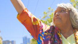 Foto einer Frau an einem Sonnigen Tag aus einer Froschperspektive. Ihr rechter Arm ist erhoben. She trägt Lidschatten und ihre Haare sind silberfarben. Sie trägt eine Bluse in bunten Farben. Im Hintergrund sind unscharf Baumwipfel und Gebäude zu erkennen.