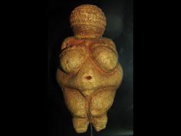 Eine erdfarbene Skulptur mit fülligem Körperbau. Der Bauchnabel ist sichtbar und die Brüste sind besonders ausgeprägt. Es fehlen Arme und Gesichtszüge.
