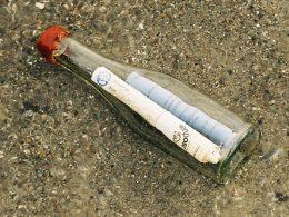 Glasflasche auf Sanboden liegend mit zwei beschrifteten Papierrollen im inneren der Flasche