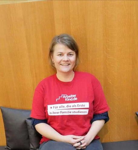 """Arbeiterkind.de, Junge Frau in rotem T-Shirt mit der Aufschrift """"Für alle, die als erste in ihrer Familie studieren"""""""
