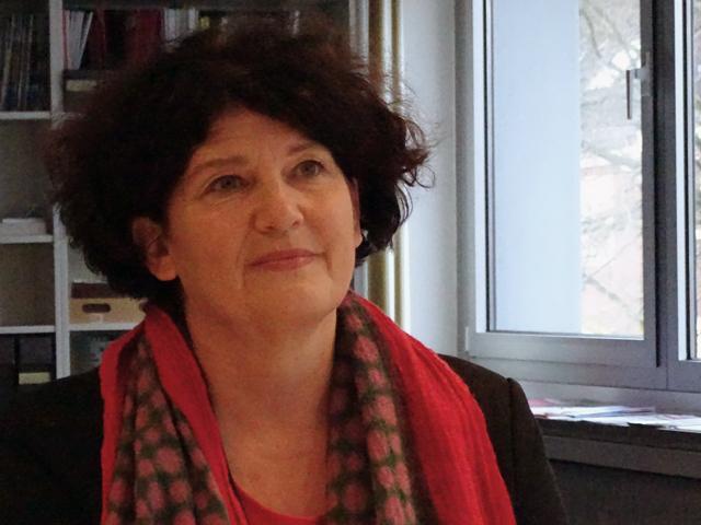 Farbfoto von Bettina Wilhelm vor einer Bücherwand und einem Fenster mit rotem Schal