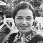 afroamerikanische Frau mit Brille sitzt im Vordergrund, hat eine getreifte Bluse an, im Hintergrund sitzt ein afroamerikanischer Mann seitlich zu der Frau, Rosa Parks
