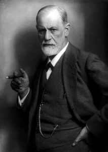 Ein Foto in Graustufen. Ein Mann mit Bart und Glatze hält eine Zigarre auf Brusthöhe. Seine linke Hand ist in seiner Hosentasche. Er trägt einen Anzug aus dem frühen zwanzigsten Jahrhundert.