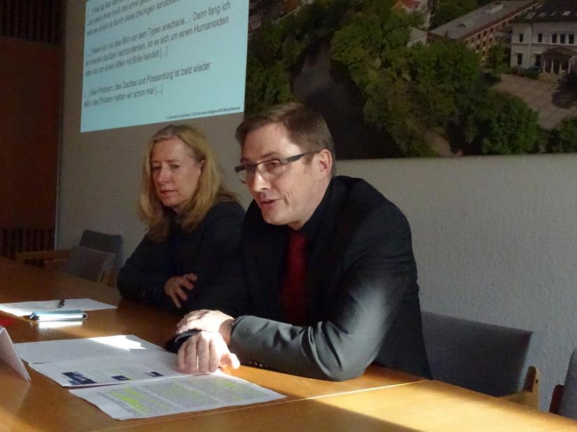 Eine Frau und ein Mann in Anzügen sitzen an einem Schreibtisch, vor ihnen liegen einige Zettel Papier. Im Hintergrund ist eine Präsentation auf eine Wand projeziert.