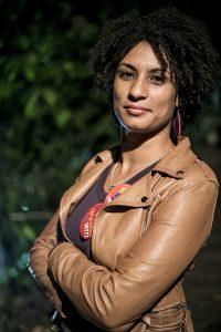 Marielle Franco, afrobrasilianische Frau mit hellbrauner Lederjacke verschränkt die Arme und lächelt in die Kamera