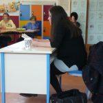Frau mit schwarzen Haaren hält Vortrag in einer Schulklasse
