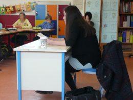Frau mit schwarzen Haaren hält Vortrag in einer Schulklasse, Scharajeg Ehsasian liest aus ihrem Buch vor