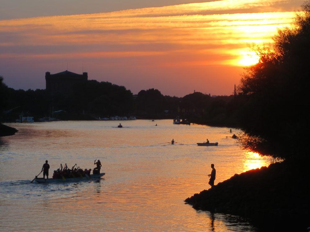 Ein Angler im Sonnenuntergang am Ufer der Weser, auf dem Fluss ein Drachenboot
