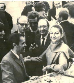 Schwarz Weiß Fotot von Maria Callas, die zwischen vielen Männern an einer Theke steht