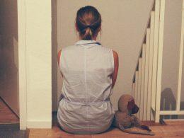 Angst Eine Frau sitzt auf der obersten Stufe einer Treppe. Neben ihr sitzt ein Kuscheltier-Affe. Man sieht die beiden nur von hinten