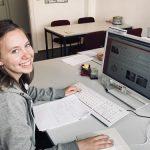junge Frau sitzt am Computer und lächelt in die Kamera
