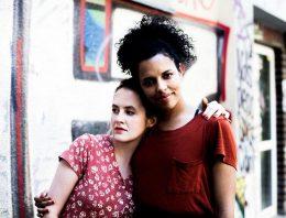 Macherinnen von Feuer und Brot: Maxi links und Alice rechts haben den Arm umeinander gelegt und stehen vor einer Wand mit Graffiti