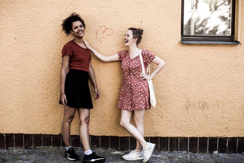 Alice links und Maxi links stehen vor einer Hauswand und lachen