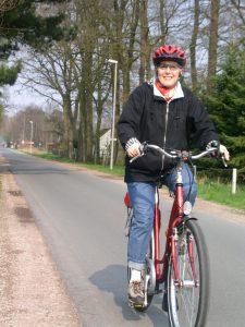 eine ältere Frau fährt mit einem roten Fahhrad. Sie trägt einen Helm.