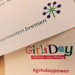 Auf einem Zettel sieht man das Girls'Day Logo, darunter steht Mädchenzukunftstag und #girlsdaypower. Auf einem anderen Zettel ist das Logo der frauenseiten.bremen zu sehen