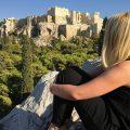 Frau sitzt auf einem Stein und schaut auf die Akropolis