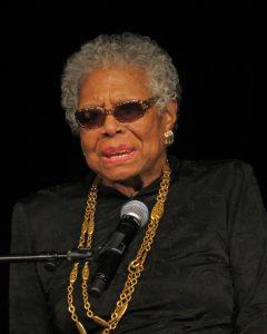 Singende Frau vor einem Mikrofon. Sie trägt eine Sonnenbrille und eine große Goldkette