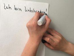 """Linke Hand schreibt """"Ich bin Linkshänderin"""""""