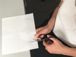 eine linke Hand schneidet ein Blatt Papier