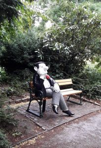Figur sitzt auf einer Bank