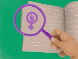 Lila Lupe wird von einer Hand gehalten, darunter liegt ein Heft mit Schrift. In der Lupe ist die Feminismus-Faust zu sehen