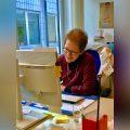 Irene wie sie lachend vor ihrem Computer sitzt mit verschwommenen Hintergrund