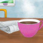 Ein rosafarbener Becher mit Kaffee steht auf einem Tisch. Daneben liegt eine Zeitung. Im Hintergrund sieht man zwei lila Stuhllehnen und einen Ausschnitt eines Fensters