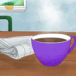 Ein lilafarbiger Becher mit Kaffee steht auf einem Tisch. Daneben liegt eine Zeitung. Im Hintergrund sieht man zwei lila Stuhllehnen und einen Ausschnitt eines Fensters
