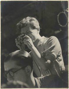 Foto von Gerda Taro, mit der Kamera vor dem Auge, wärend sie eine Aufnahme macht