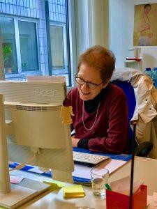 Irene wie sie lachend vor ihrem Computer sitzt