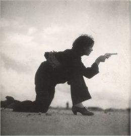 Aufnahme von Gerda Taro, von einer bewaffneten Frau, die auf dem Boden kniet, mit einer Pistole in der Hand