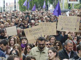 Menschenmenge auf einer Demonstration. Im Hintergrund schwenken Teilnehmer*innen lila Flaggen im Vordergrund werden Pappschilder mit spanischen Sprüchen hochgehalten