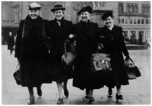 Vier Frauen in dunklen Mänteln laufen fröhlich über den Bremer Marktplatz, 1946