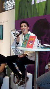 Foto von Francesca Cavallo, einer Autorin mit schwarzen kurzen Haaren, die auf einem Hocker sitzt und ins Mikro spricht. Sie schaut dabei direkt in die Kamera. Vor ihr steht ein Tisch, auf dem zwei Bücher zur Pärsentation stehen. Daneben ein Wasserglas.