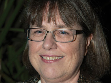 Eine lächelnde Frau mit braunen mittellangen Haaren, die eine Brille trägt. Donna Strickland
