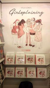"""Poster eines Buchcovers an einer Wand. Darauf zu sehen: Fünf Mädchen*. Eine von ihnen hat ihre Unterhose hinuntergezogen, die anderen schauen sie an. Über den Mädchen steht """"Katja Klengel"""" und darunter """"Girlsplaining"""""""
