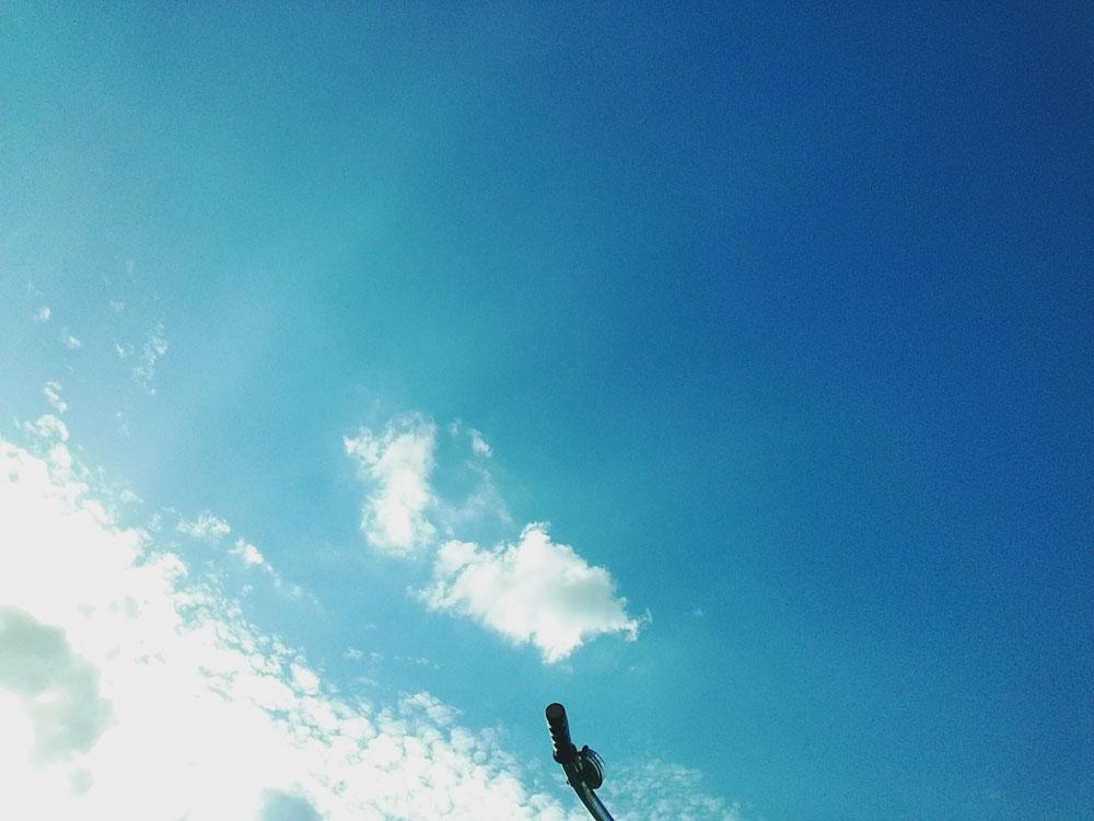 Foto von einem blauen Himmel. Auf der linken unteren Hälfte sind weiße Wolken. Unten in der Mitte sieht man einen Teil eines Fahrradlenkers.
