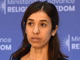 Eine Frau mit dunkelbraunen Haaren steht vor einem Mirofon und hält vermutlich gerade eine Rede