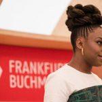 Foto von der Eröffnungsveranstaltung der Frankfurter Buchmesse. Eine lächelnde Frau steht am Mikrophon.
