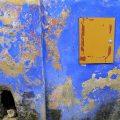 """Die Fotografie """"Wandwerk"""" der Künstlerin Regina Contzen, die Teil der Werkschau Blick.Art in der ZGF ist. Es zeigt eine leicht heruntergekommene Wand, die zum größten Teil blau ist. An einigen Stellen ist die Farbe jedoch abgeblättert. Andere Stellen sind gelb."""
