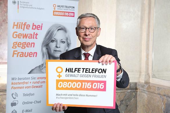 """Bürgermeister Sieling hält einen Schild hoch mit der Aufschrift """"Hilfetelefon"""" -Gewalt gegen Frauen"""