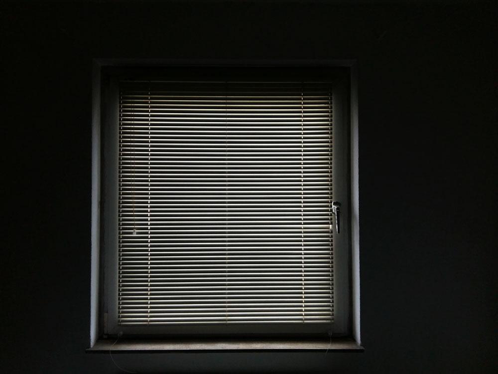 Sexueller Mißbrauch Ein Foto eines Fenster. Die Jalousie ist runter gelassen. Licht wird durch die Lamellen geworfen