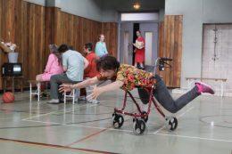Tanzszene Amour, Frau liegt auf Rollator mit ausgestreckten Beinen und Armen